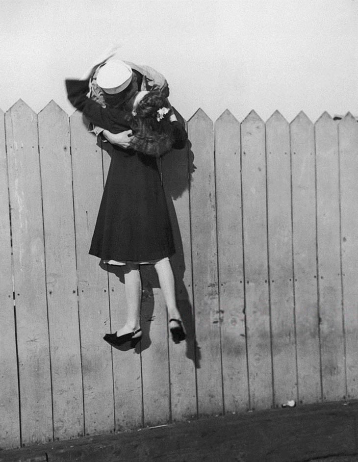 A Sailor Leans Over A Picket Fence And Lifts His Girlfriend Up For A Kiss, 1945
