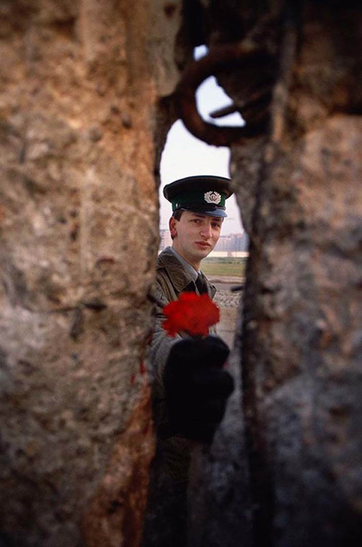 1989 - East German soldier passing a flower through the Berlin Wall before it was torn down.